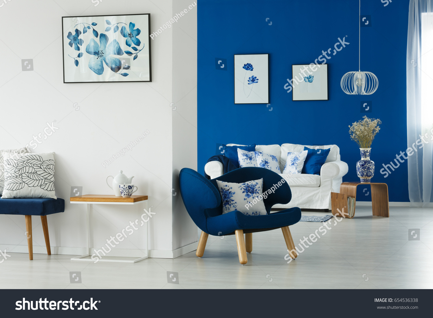 cozy blue white living room flowery stock photo 654536338 cozy blue and white living room with flowery patterns on pillows and posters