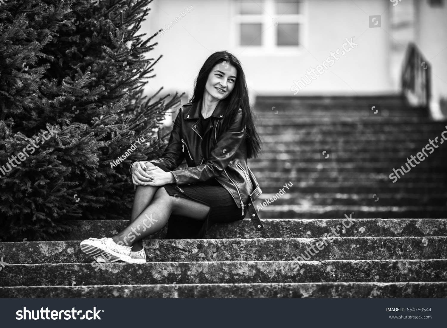 Portrait of young pretty white girl with black hair and in black clothes posing on the