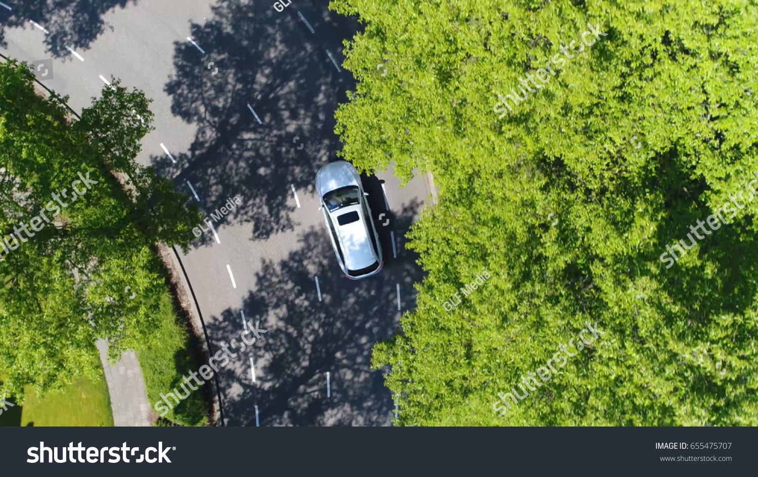 Aerial following car top-down view this grey colored station wagon is driving over two way street corner green trees on both sides of street #655475707