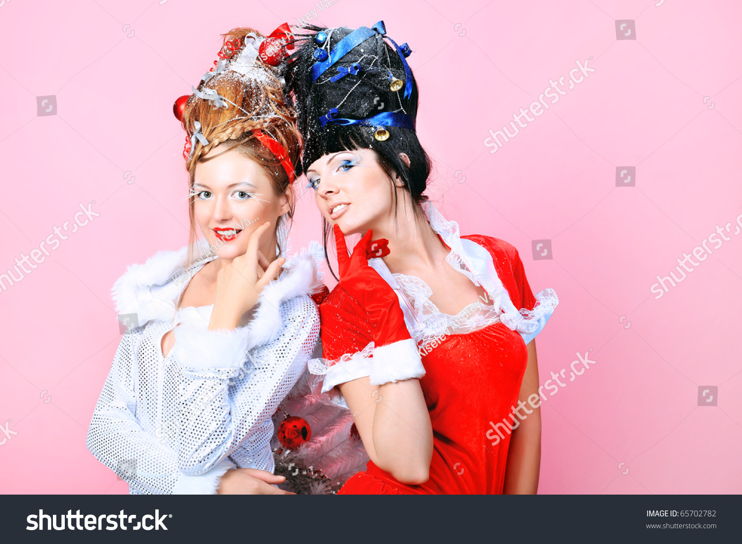 two beautiful young women in christmas clothes posing over pink background