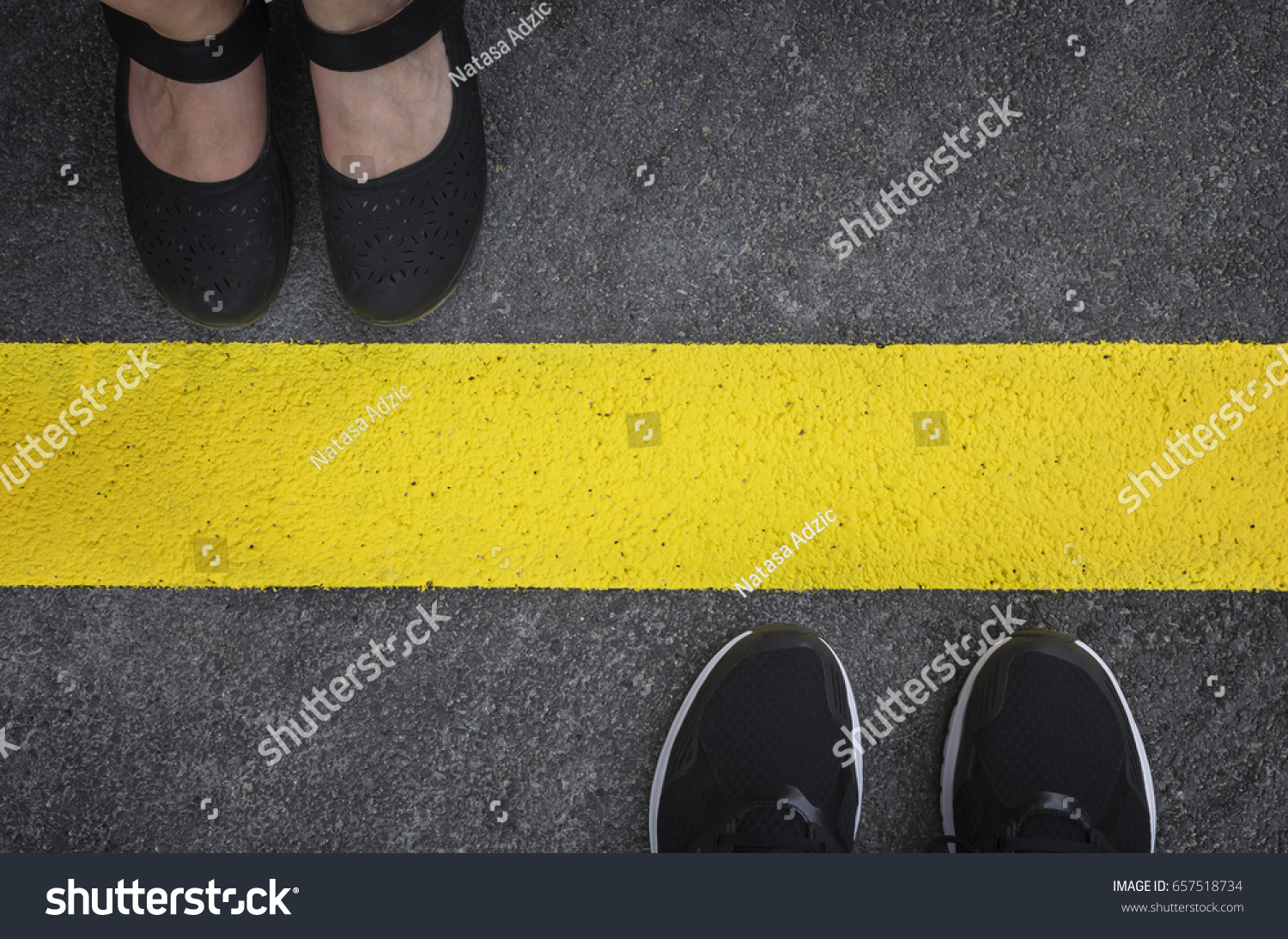 Legs of a couple standing opposite each other divided by the yellow asphalt line top view #657518734