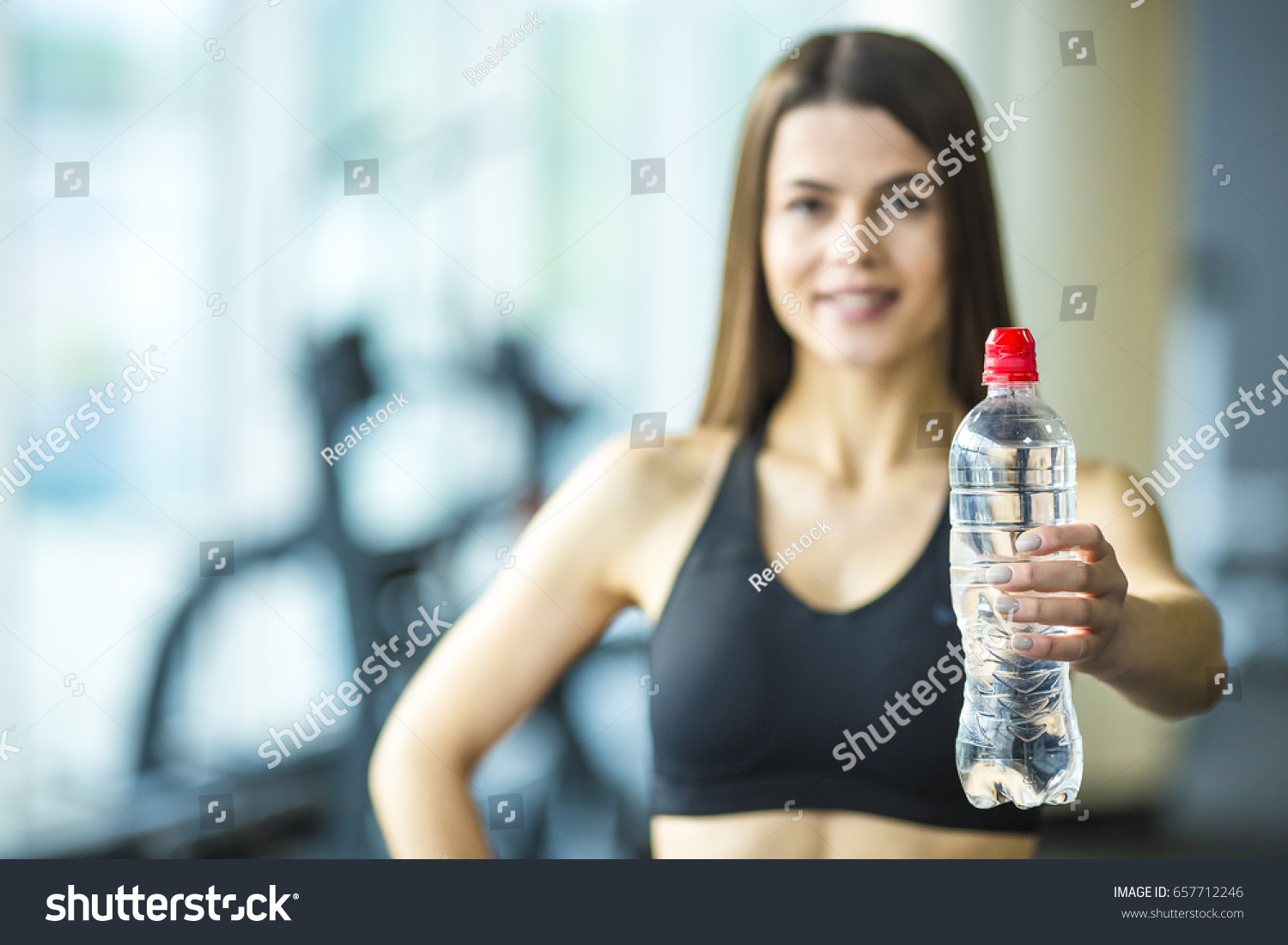 Young woman hold bottle water gym stock photo 657712246 shutterstock the young woman hold a bottle of a water in the gym sciox Gallery