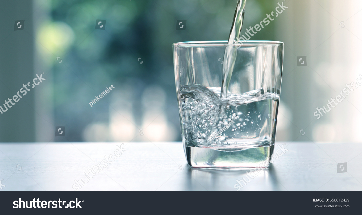 Close up pouring purified fresh drink water from the bottle on table in living room #658012429