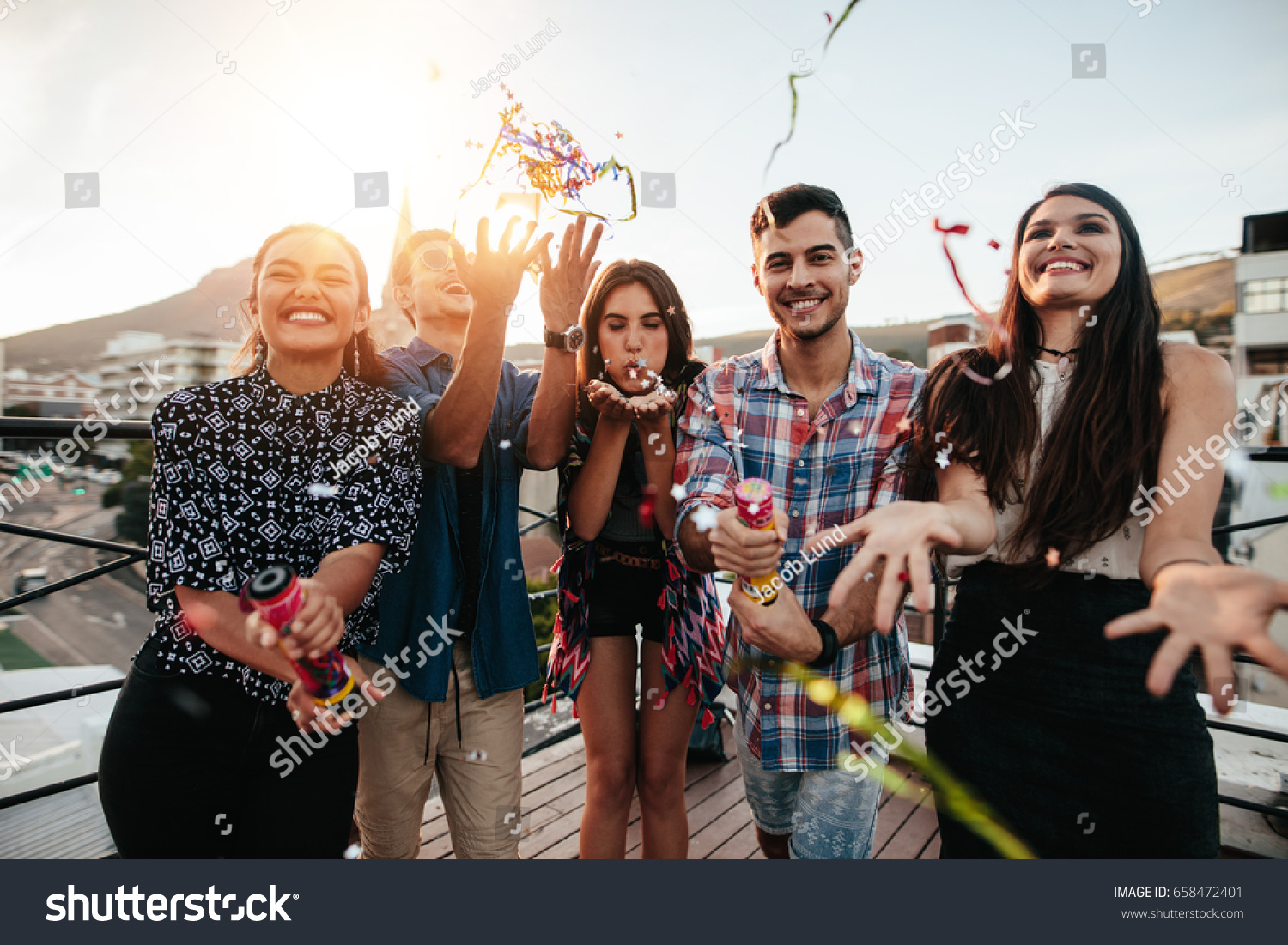 Group happy young people throwing confetti stock photo for Terrace party