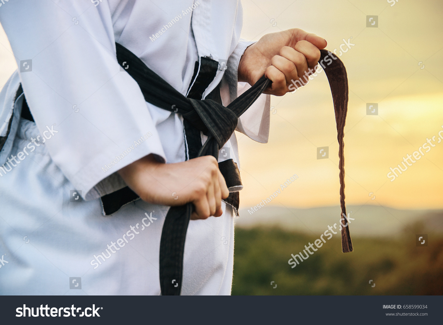 A young martial arts master knots a black belt. Close-up. Image with the effect of sunlight. #658599034