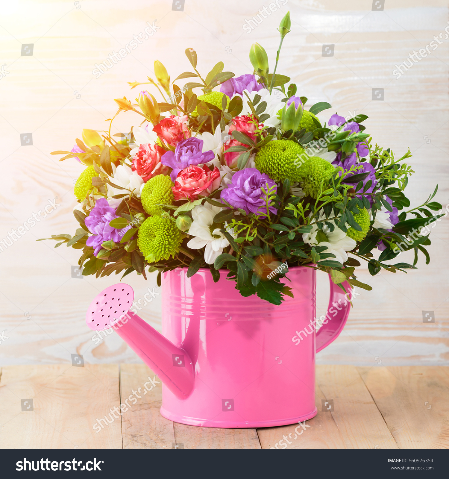 Beautiful bouquet of pink purple and white flowers in pink watering beautiful bouquet of pink purple and white flowers in pink watering can on wooden table wood background ez canvas izmirmasajfo