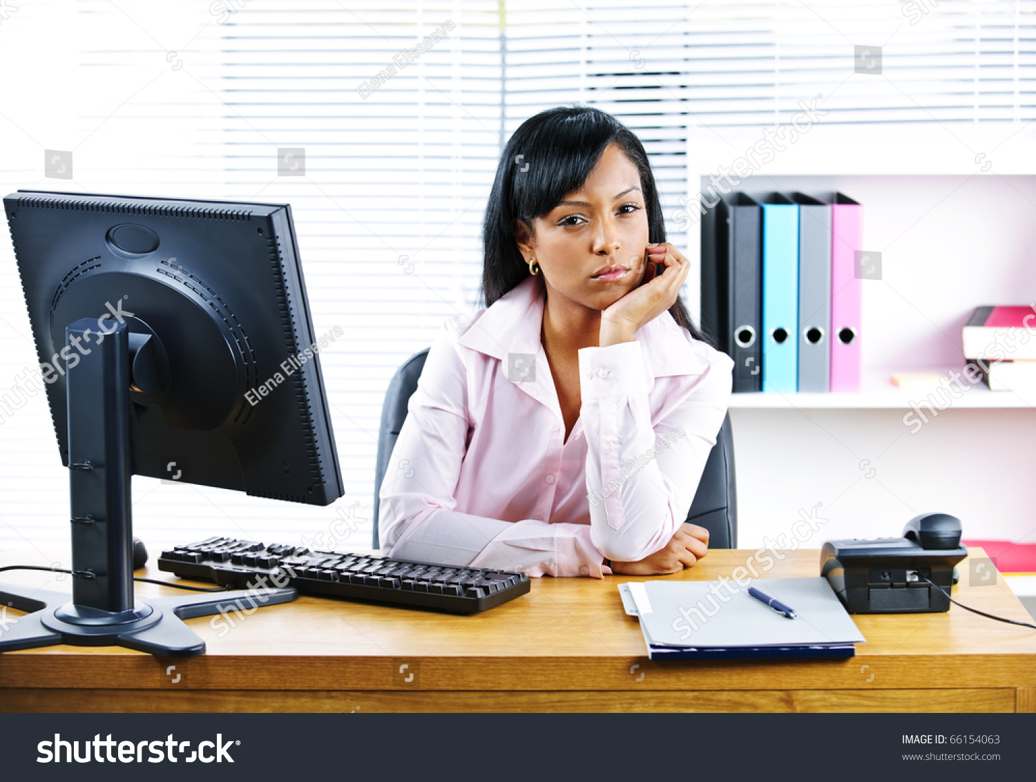 portrait of young black unhappy business w at desk in office save to a lightbox