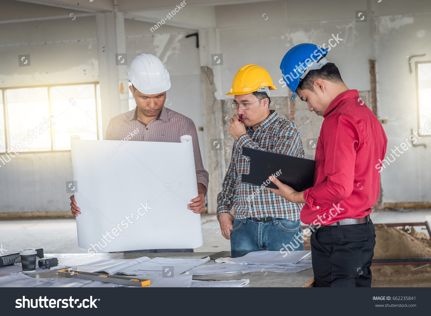 Group engineer checking blueprint on table stock photo 662235841 group of engineer checking the blueprint on the table and talking about construction project with commitment malvernweather Gallery