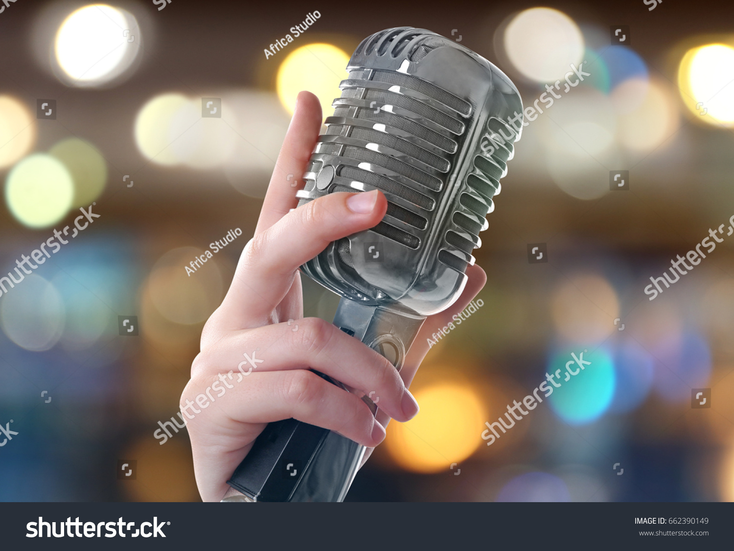 2e2f9d1ec102e Female hand with vintage microphone on blurred lights background. Concept  of Christmas music and songs