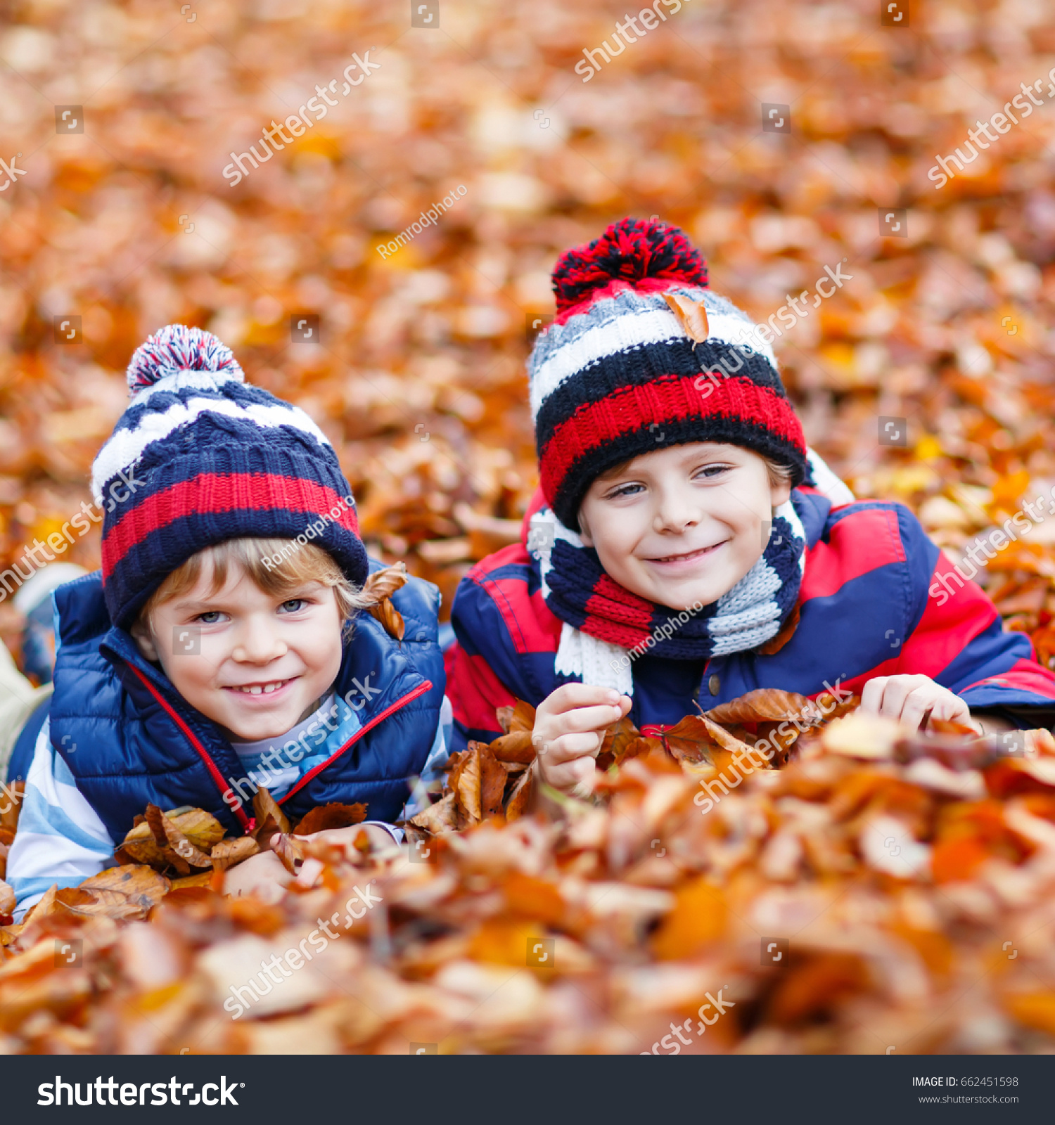 ce4ce021f53 Two little friends boys lying in autumn leaves in colorful clothing. Happy  siblings kids having fun in autumn forest or park on warm fall day. With  hats and ...
