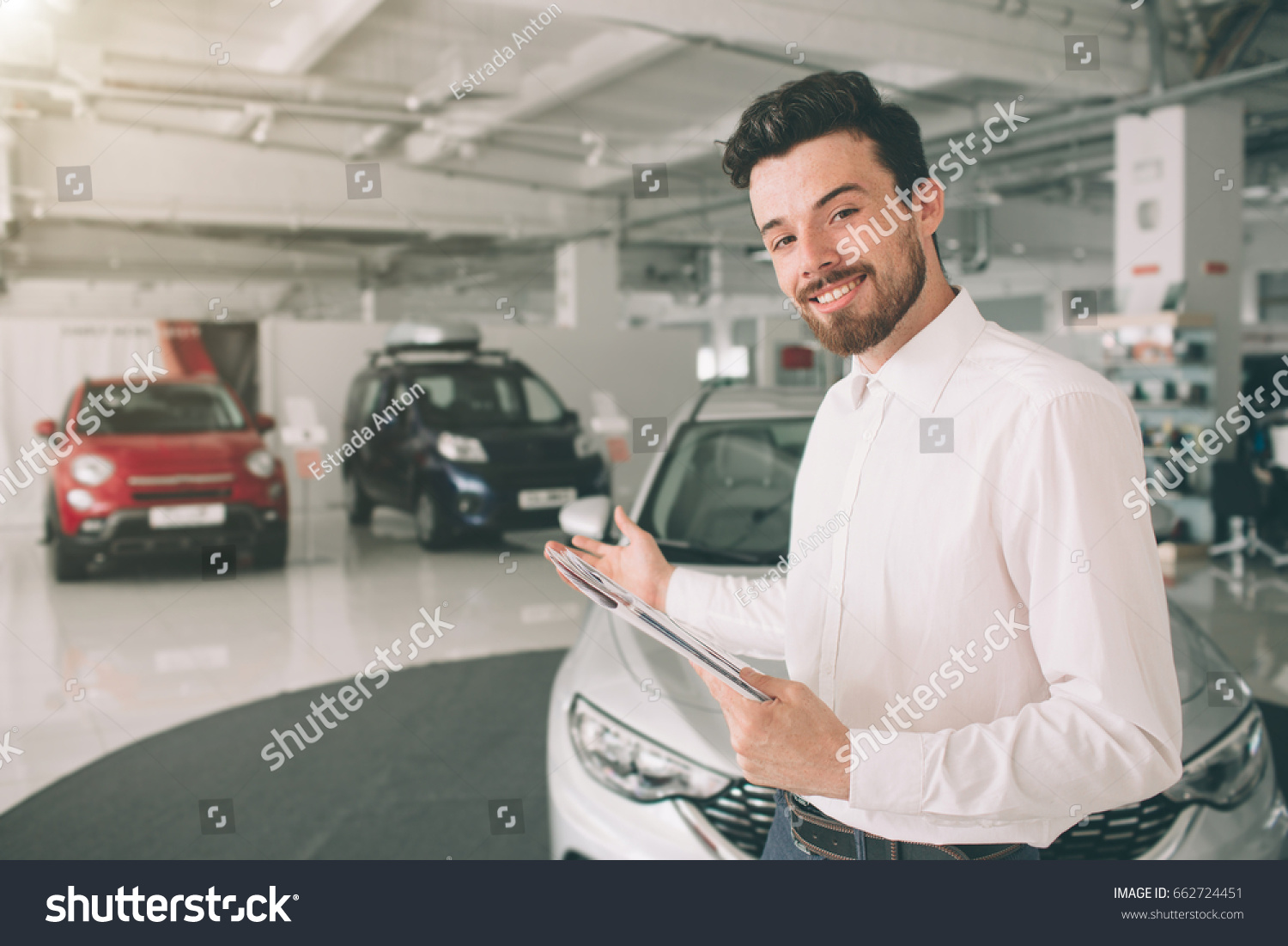 Friendly Vehicle Salesman Presenting New Cars Stock Photo