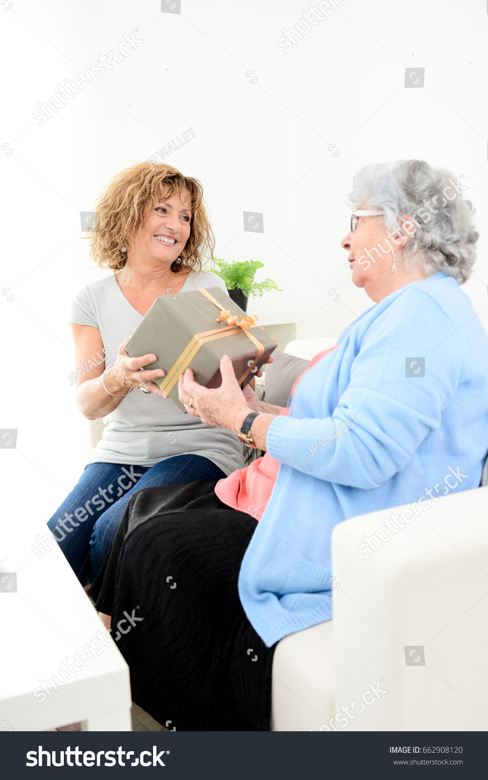 Mature Woman Offering Present Gift To Elderly Senior Lady For Mothers Day Or Birthday Anniversary