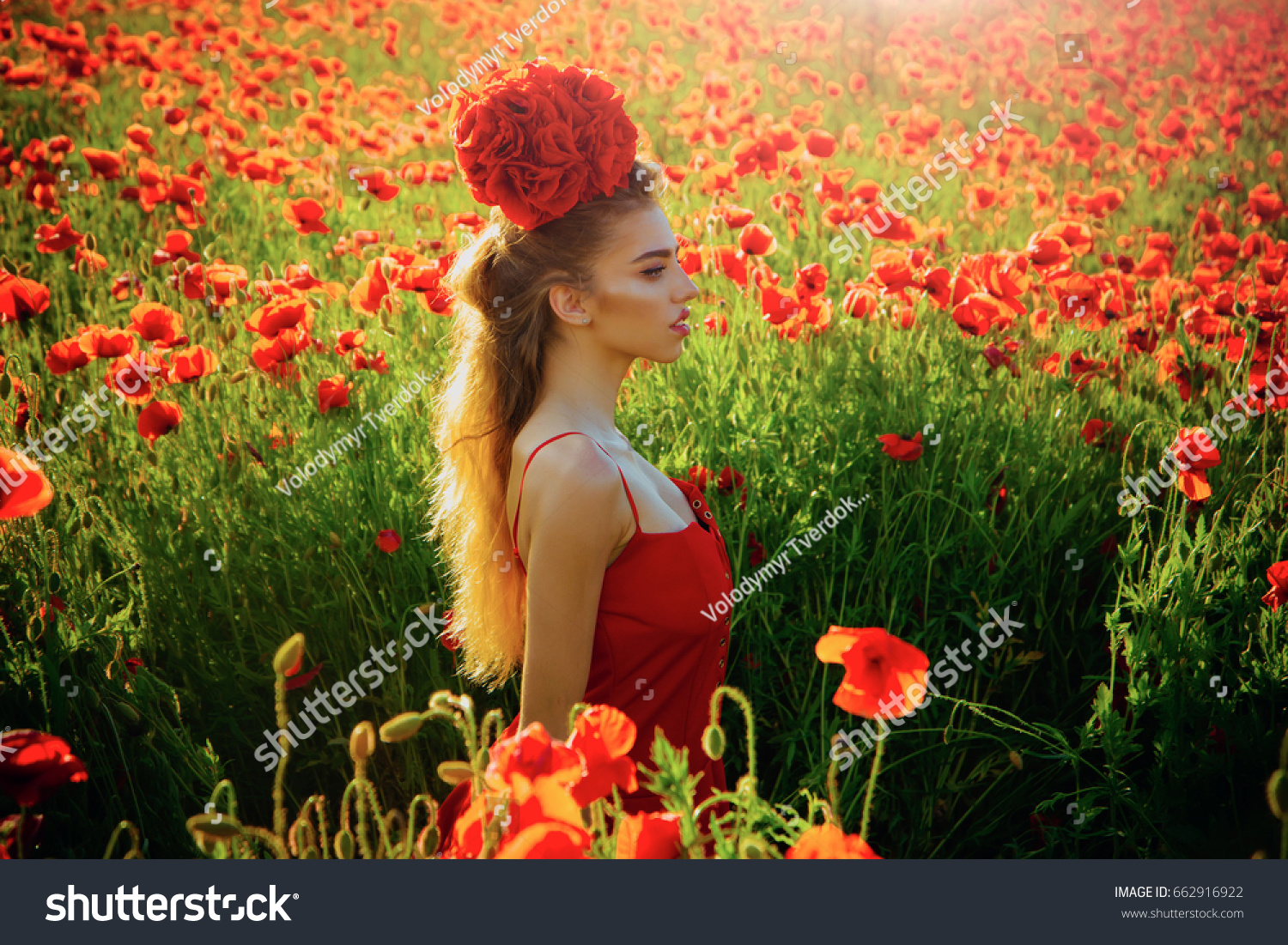 Girl With Long Curly Hair In Red Dress Hold Flower Bouquet In Field