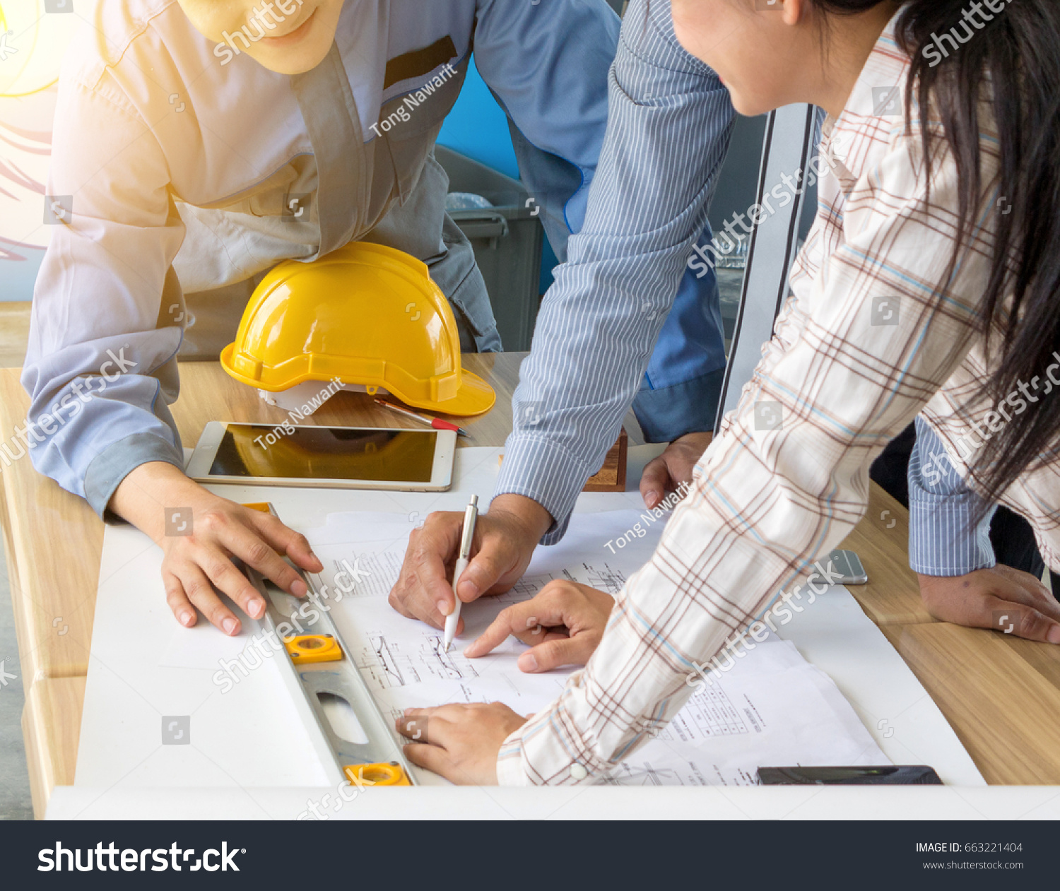 Group engineers looking blueprint construction on stock photo a group of engineers are looking at a blueprint for construction on the table engineering malvernweather Images