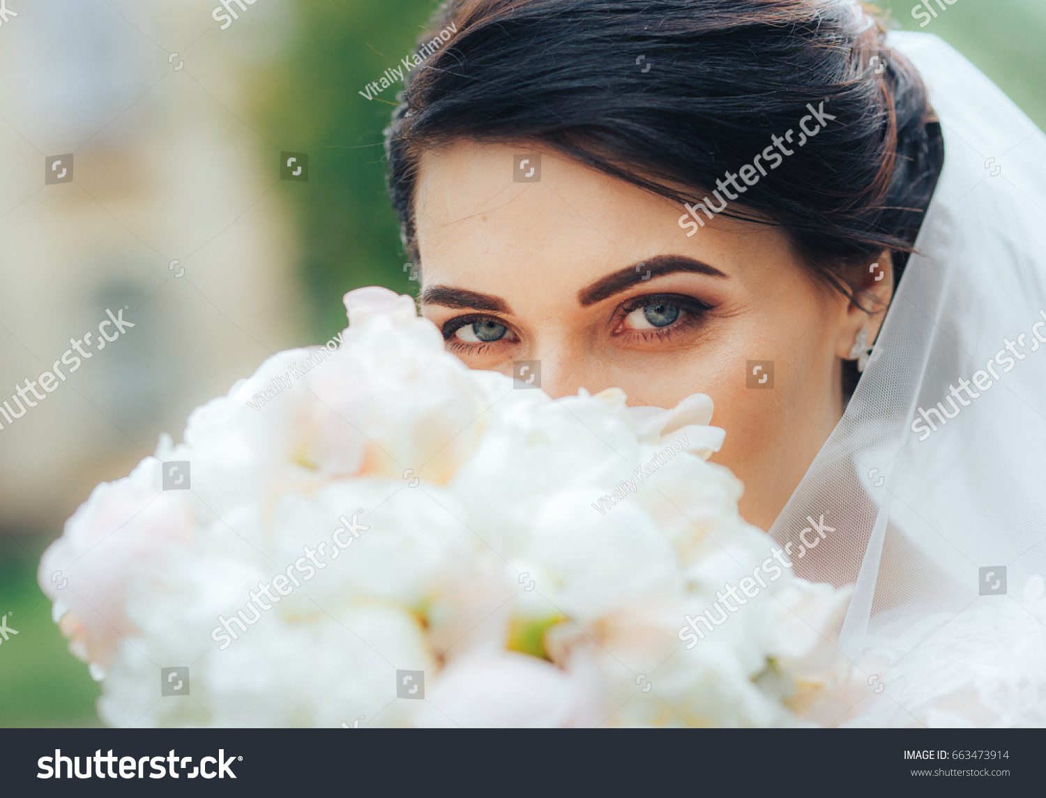 Beautiful warrior bride blue eyes looks stock photo 663473914 a beautiful warrior bride with blue eyes looks at the camera hiding behind a bouquet of izmirmasajfo Gallery