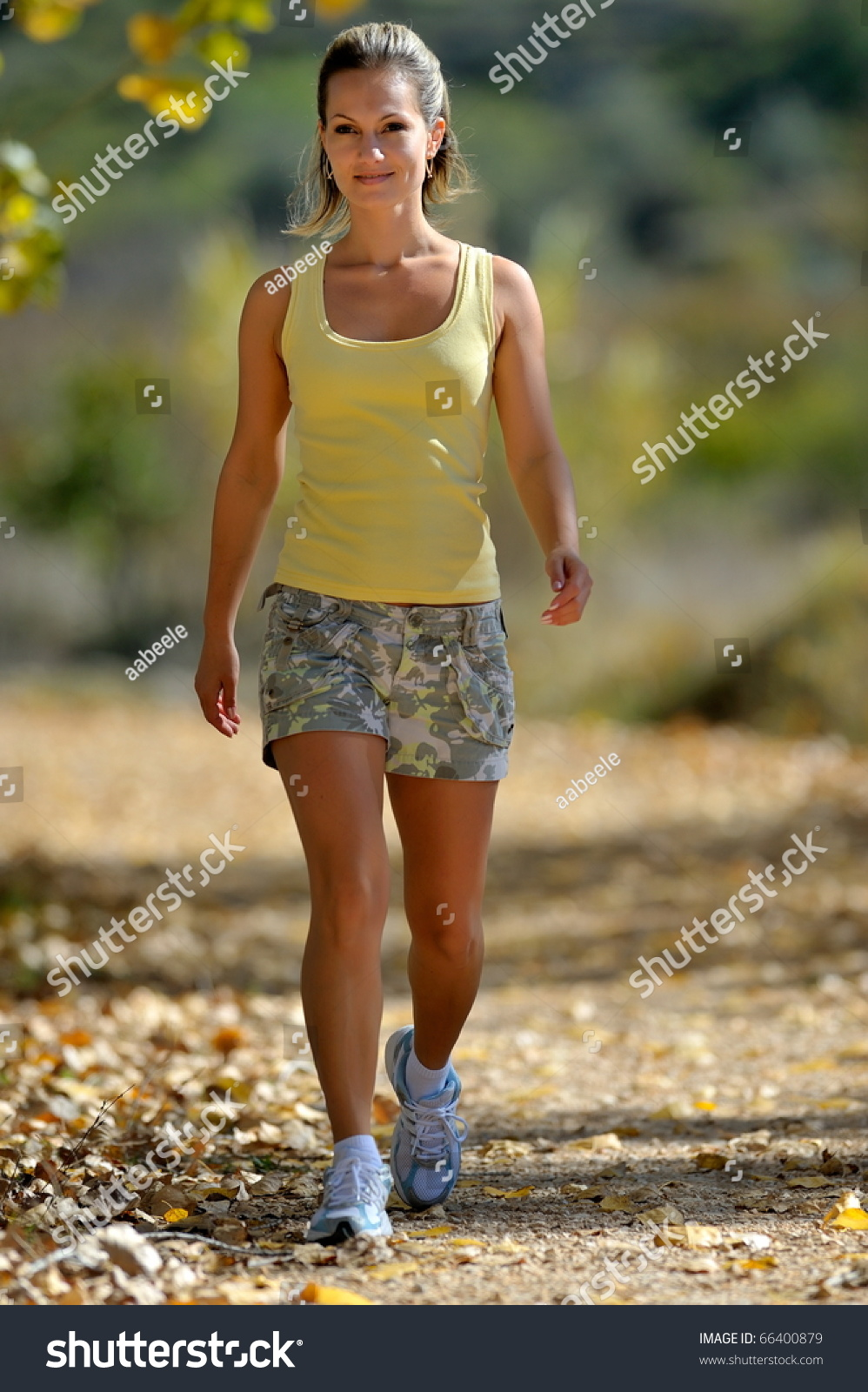 young woman walking park summer stock photo 66400879