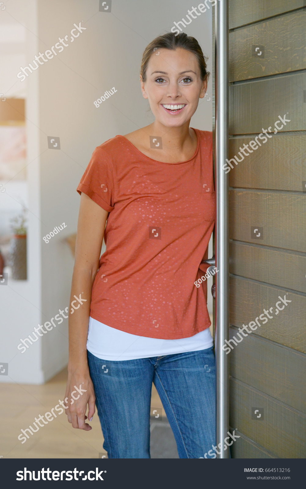 opening front door. Young Woman Opening House Front Door To Welcome People In I