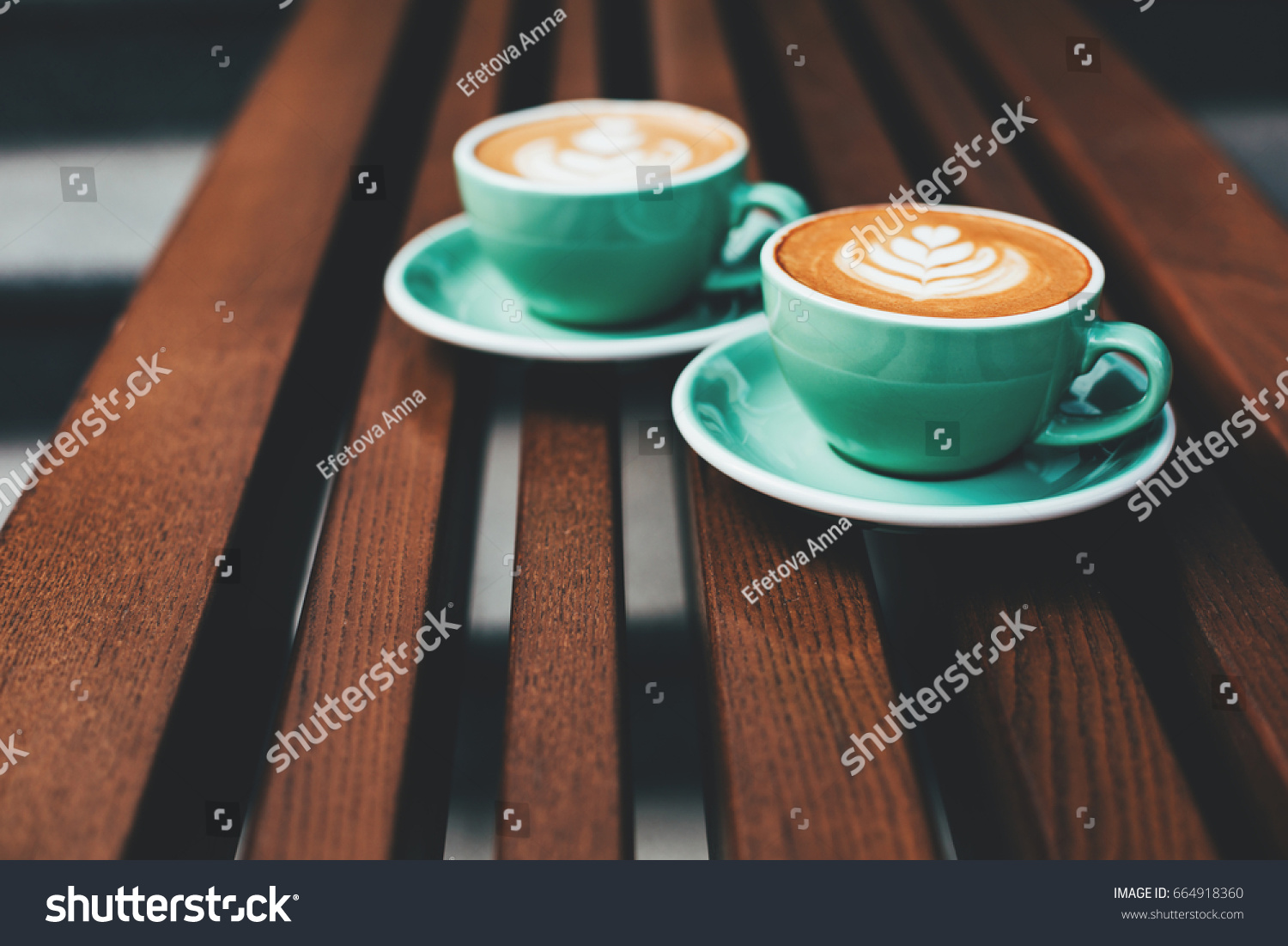 Two cups of cappuccino with latte art on wooden background. Beautiful foam, greenery ceramic cups, stylish toning, place for text. #664918360