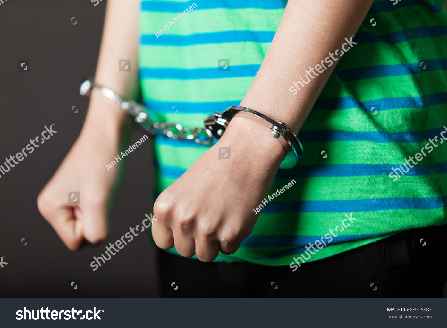 Close up on pair of hands from child or teenager in green and blue shirt tied with metal handcuffs #665976883