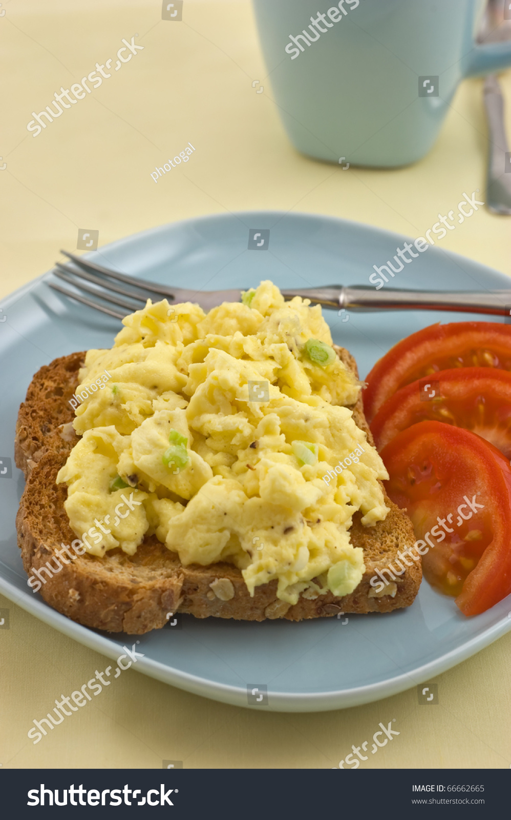 Scrambled Eggs On Whole Grain Toast With Tomato Slices In Vertical Format