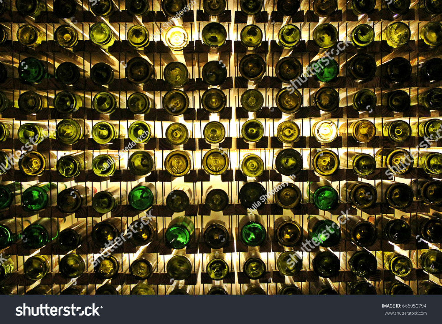 Many glass wine bottles on wine shelves with lighting. Interior in the restaurant.  Color photo