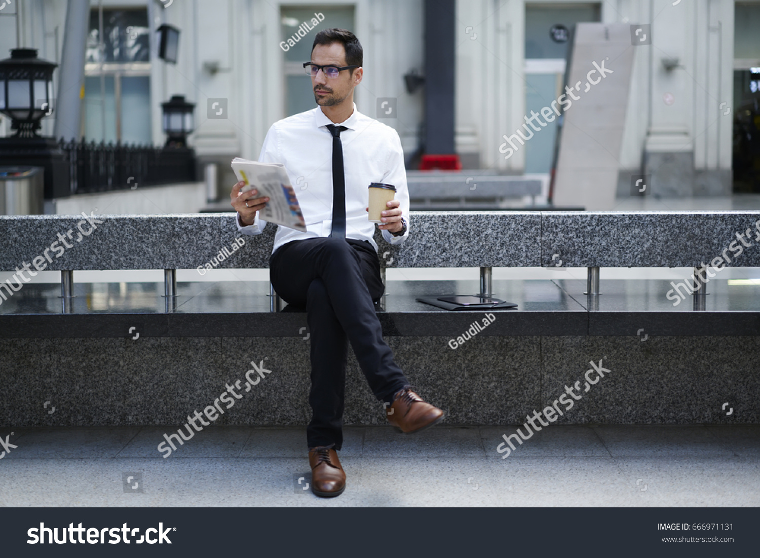bbd3c06dd04 Handsome male banker in formal outfit reading newspaper holding coffee to  go waiting for transport getting