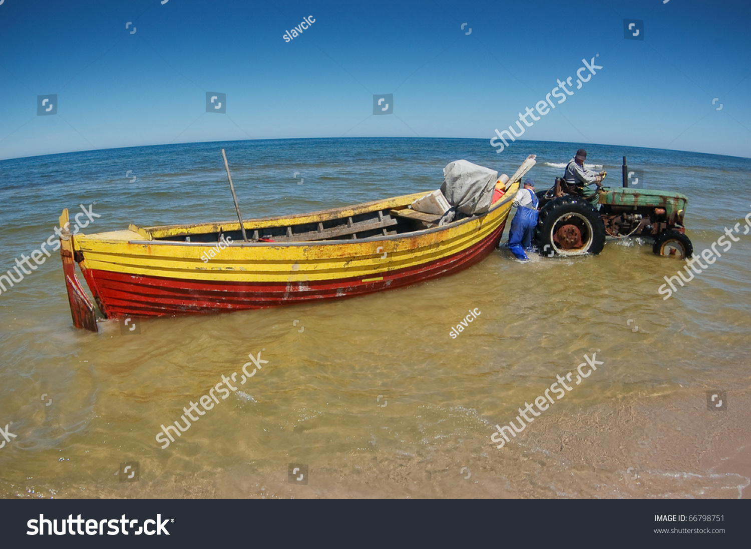 Tractor Pull Boats : Old rusty tractor pulling boat out of the sea stock photo