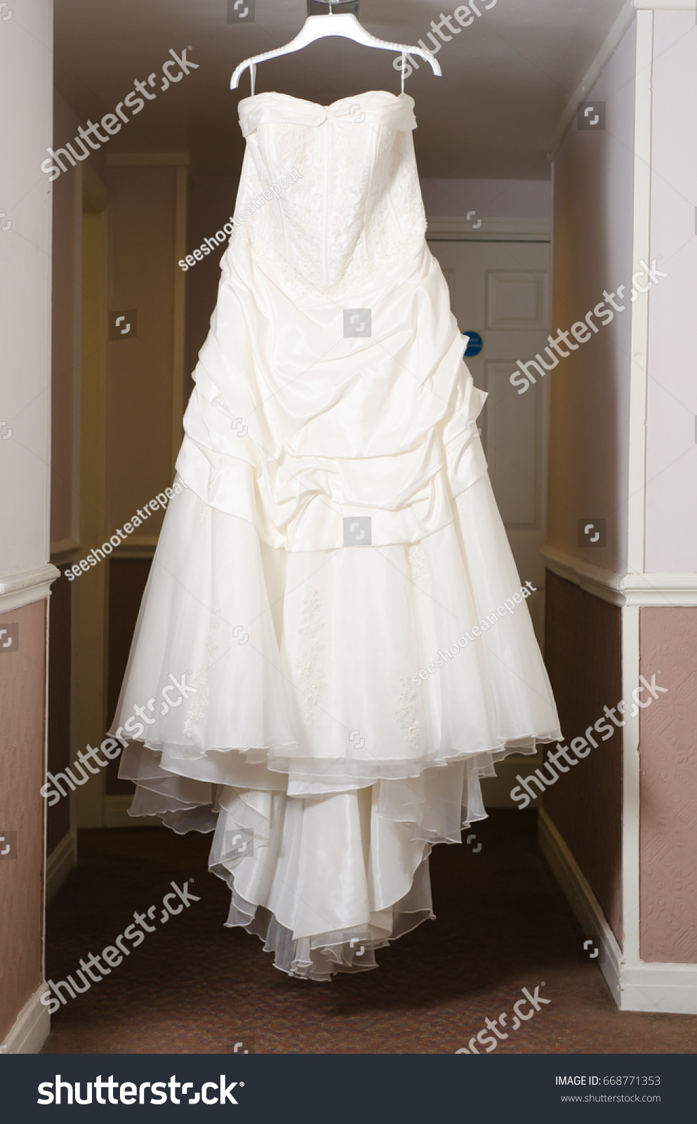 A Beautiful Cream And Clean Wedding Dress Hanging In The Hall Of Hotel Room