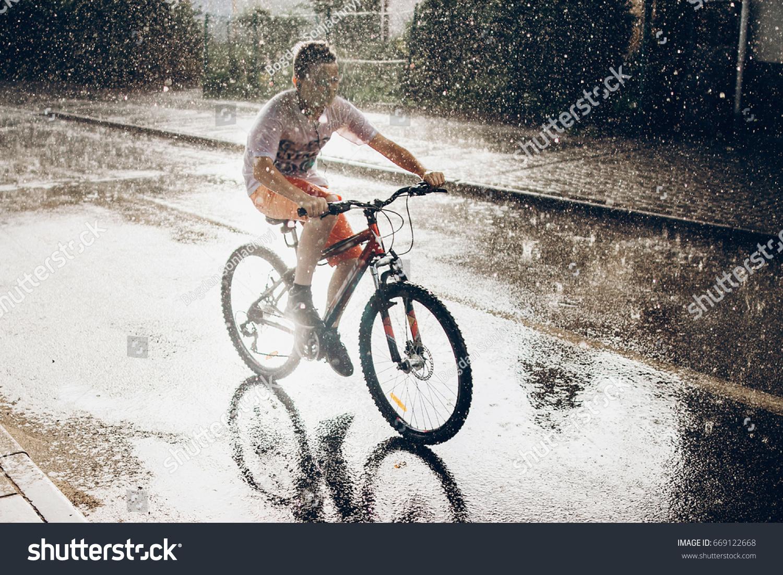 Young Boy Riding Bicycle Rainy Street Stock Photo 669122668
