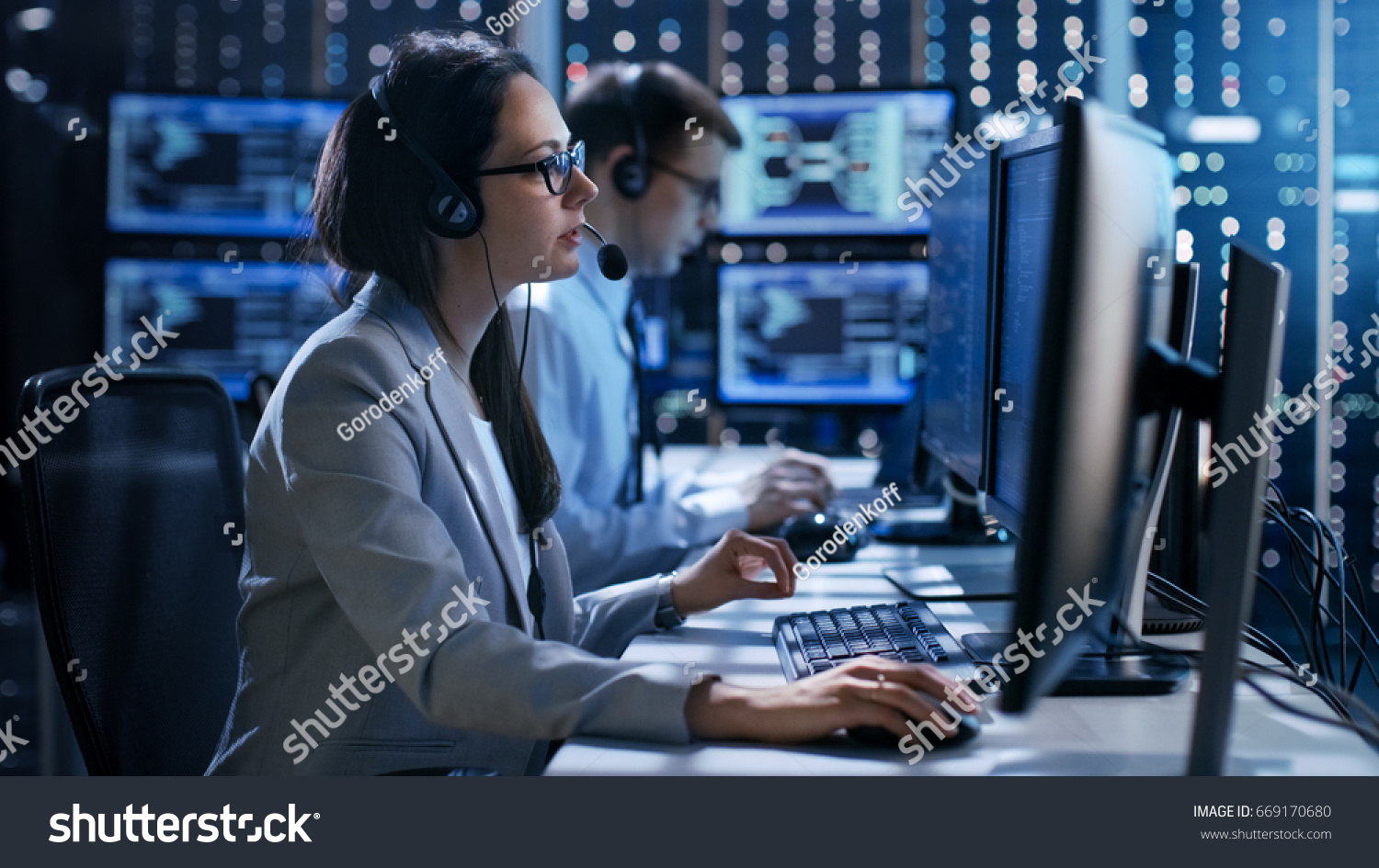 Female working in a Technical Support Team Gives Instructions with the Help of the Headsets. In the Background People Working and Monitors Show Various Information.  #669170680