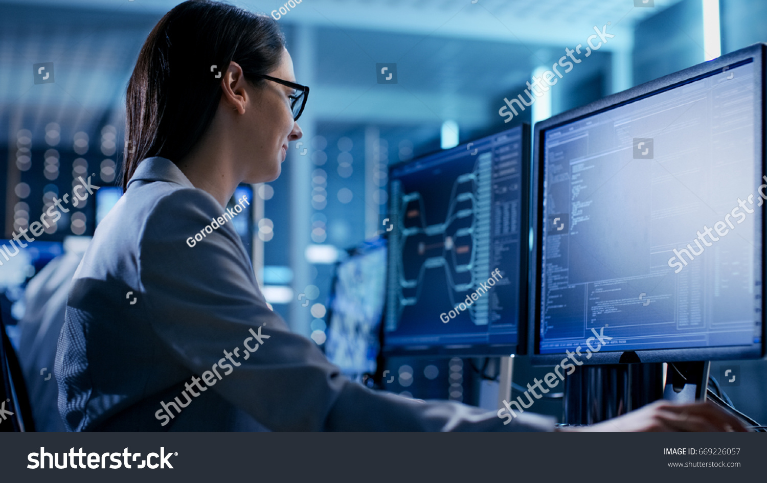 Close-up Shot of Female IT Engineer Working in Monitoring Room. She Works with Multiple Displays. #669226057