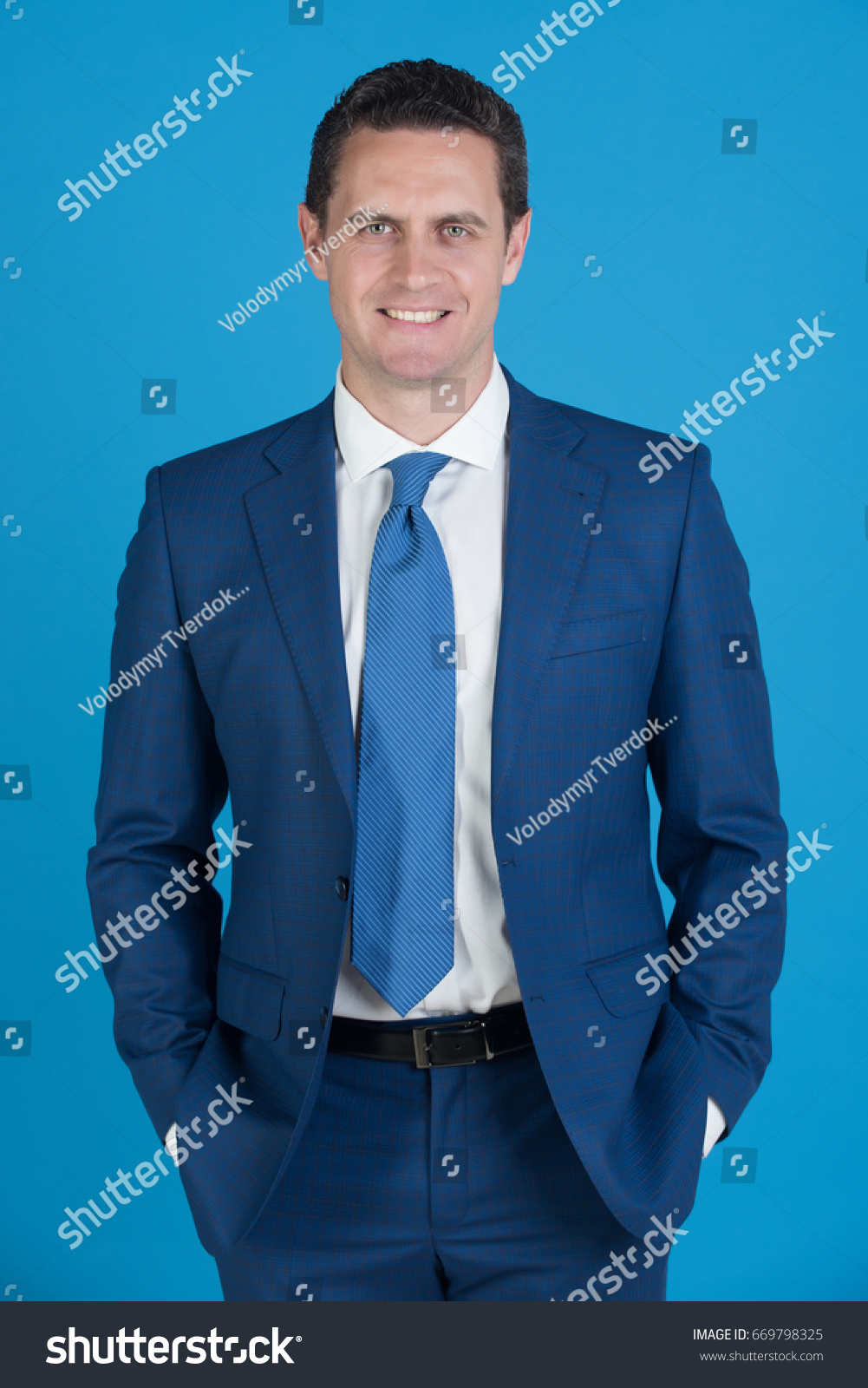 d16364970 boss smiling with hands in pockets in fashionable navy formal suit, white  shirt and tie on blue background. Business, fashion and success - Image