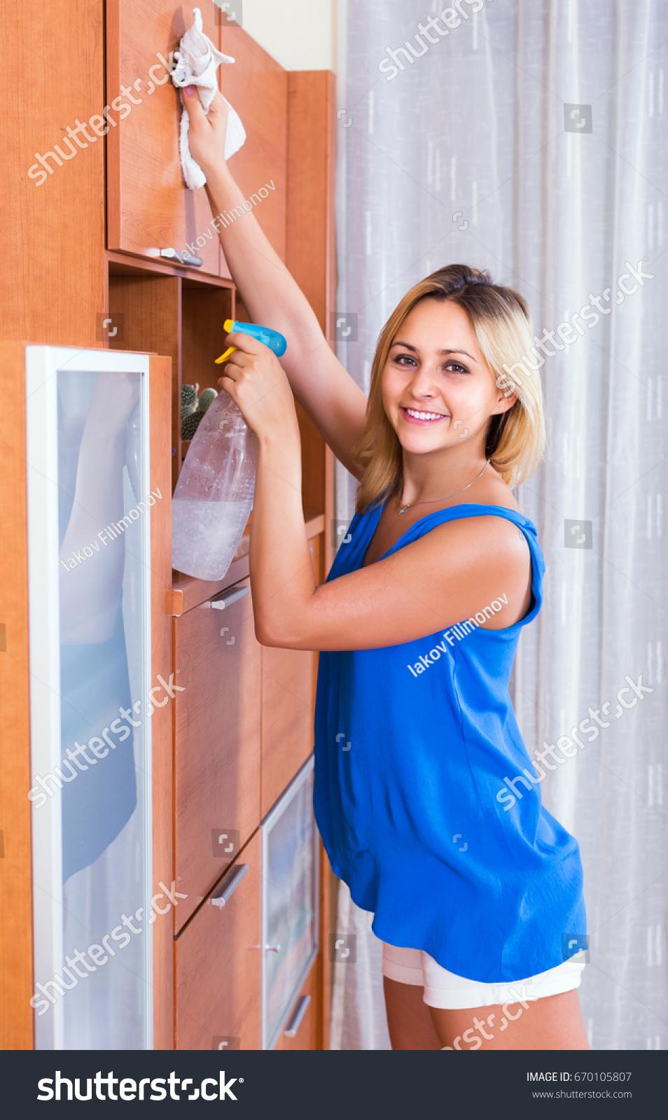 dusting furniture. Ordinary Smiling Blonde Girl In Blue Blouse Dusting Furniture Indoors