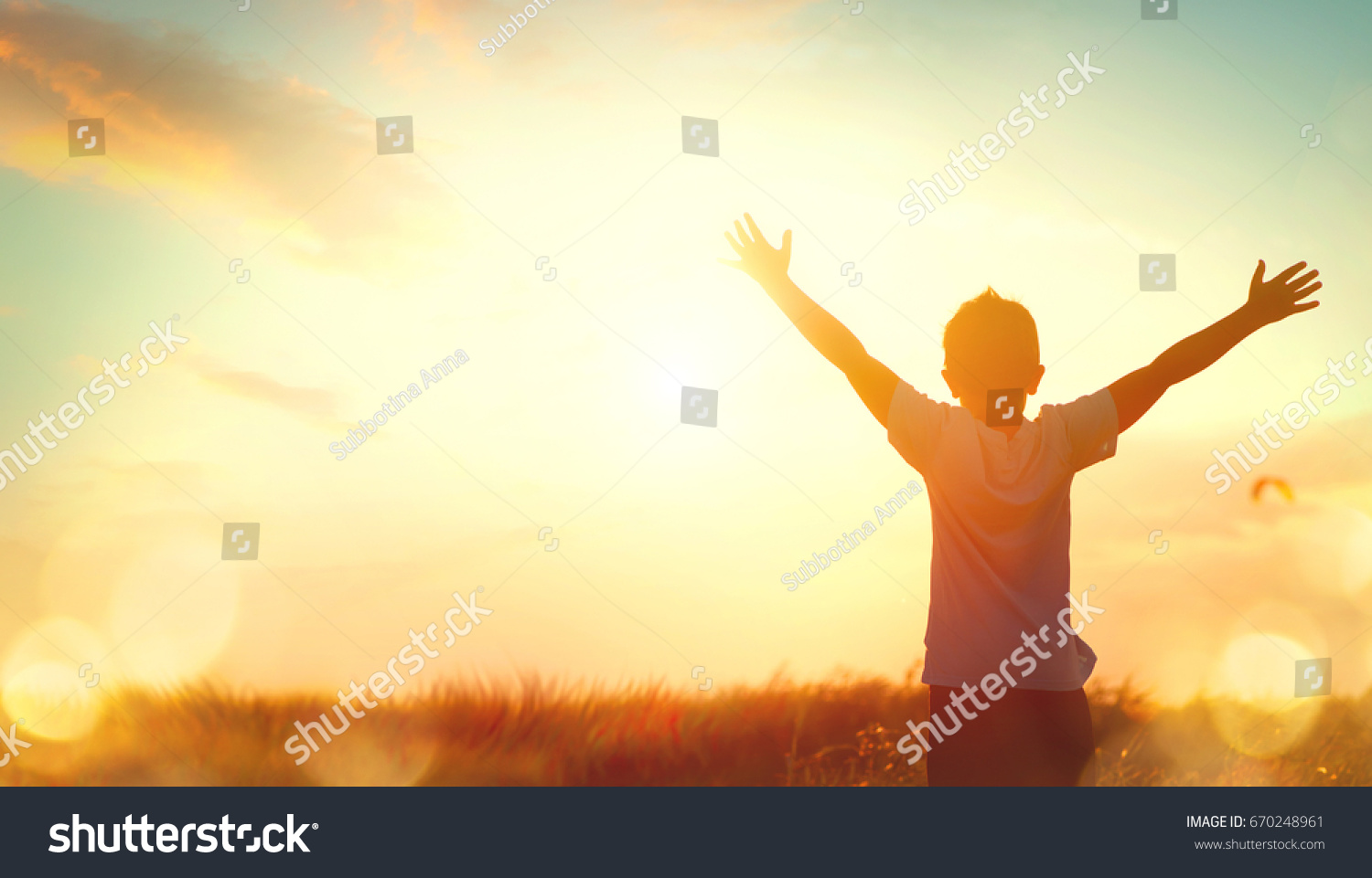 Little boy raising hands over sunset sky, enjoying life and nature. Happy Kid on summer field looking on sun. Silhouette of male child in sunlight rays. Fresh air, environment concept. Dream of flying