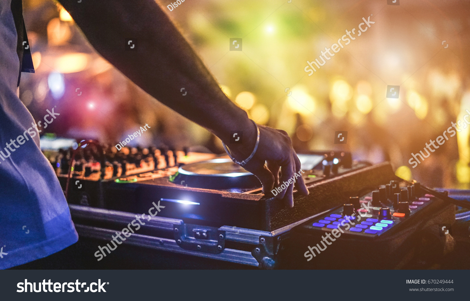 Dj mixing outdoor at beach party festival with crowd of people in background - Summer nightlife view of disco club outside - Soft focus on hand - Fun ,youth,entertainment and fest concept #670249444