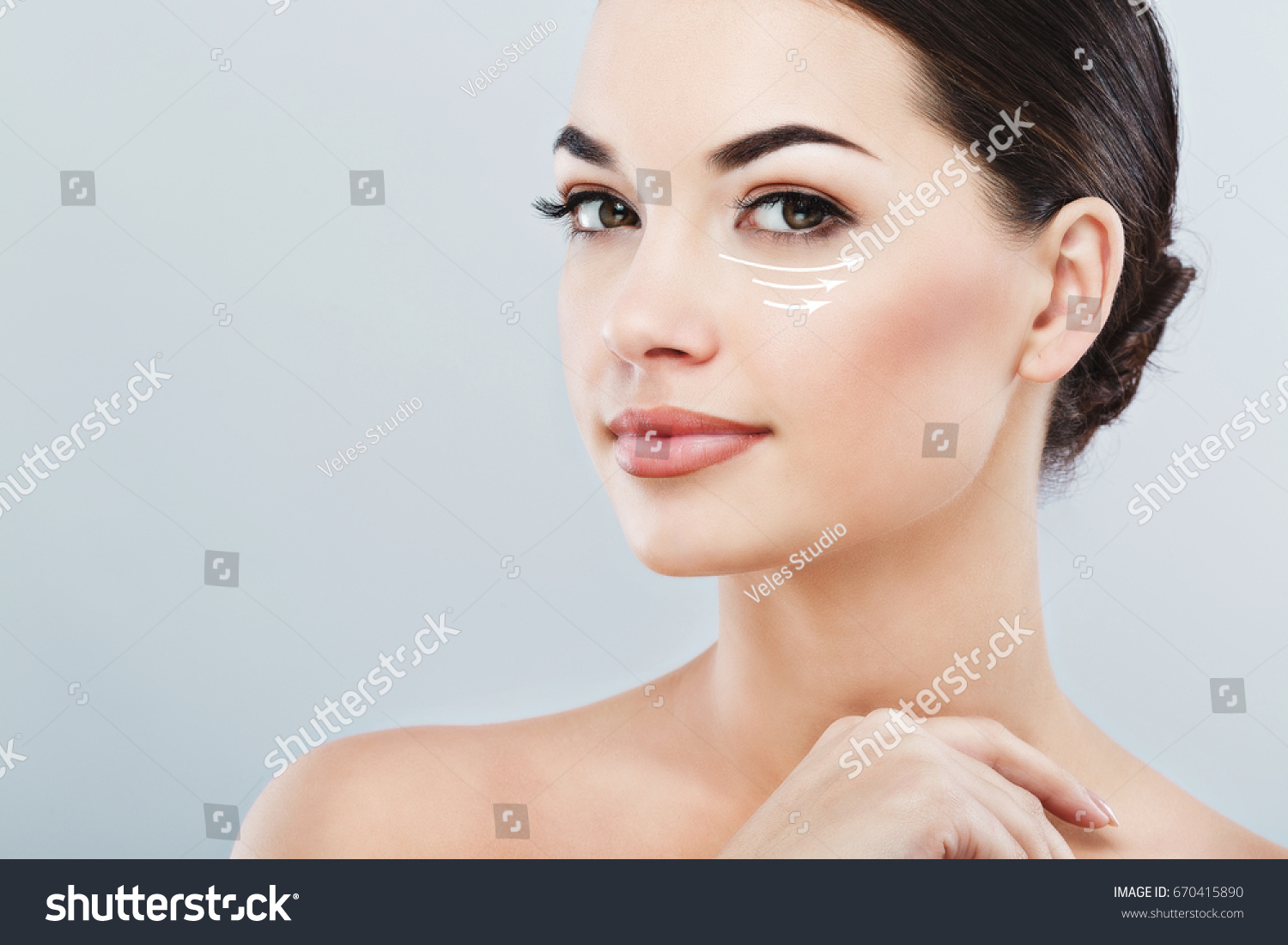 Young female with clean fresh skin, antiaging concept. Attractive girl with naked shoulders, looking at camera and smiling, holding hands near face, lifting arrows under eye #670415890