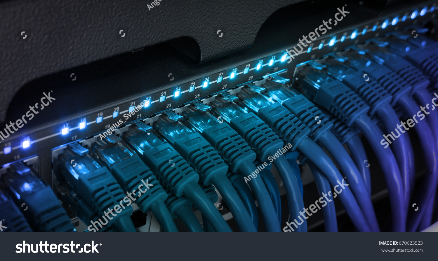 Network server panel, switch and patch cord cable in data center glowing in the dark. Blue led #670623523