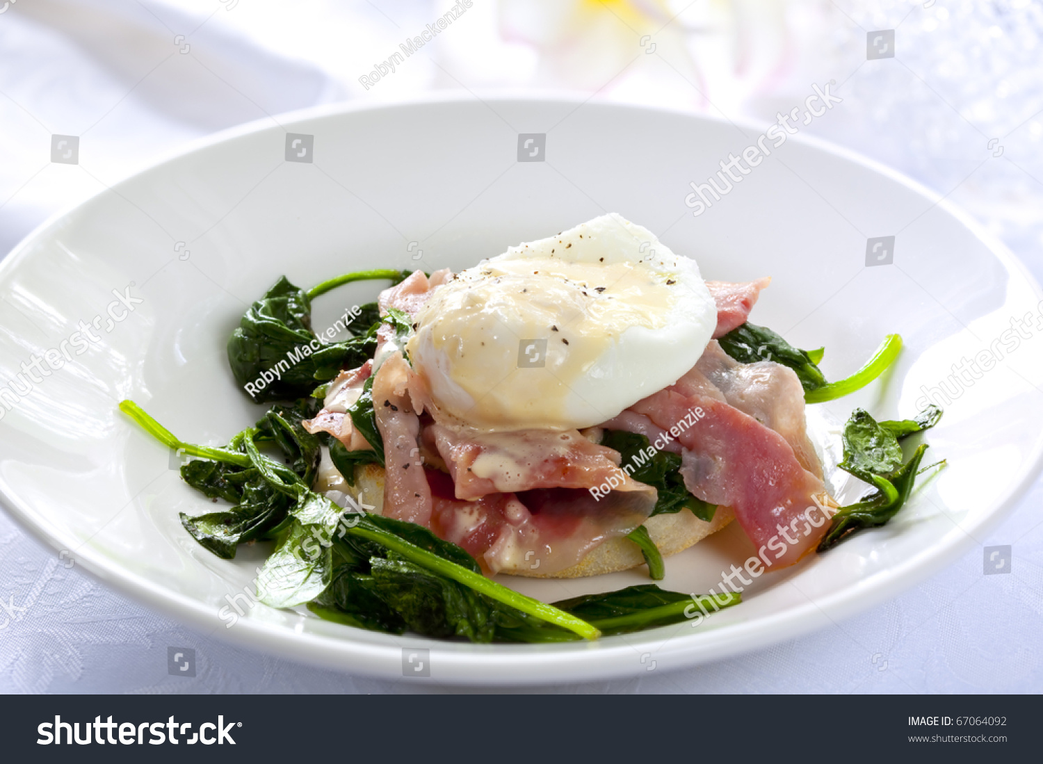 Eggs Benedict. Toasted muffin topped with wilted spinach, ham, poached ...