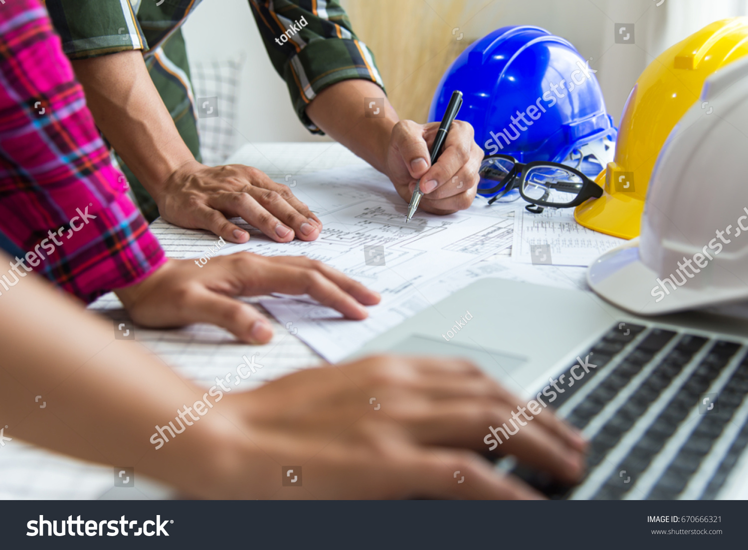 Engineer Architect working table with safety helmet,Engineer in working on computer laptop in office. #670666321