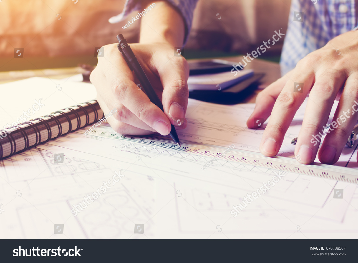 Asian man hand drawing on blueprint stock photo 670738567 asian man hand drawing on blueprint paper at home office malvernweather Image collections