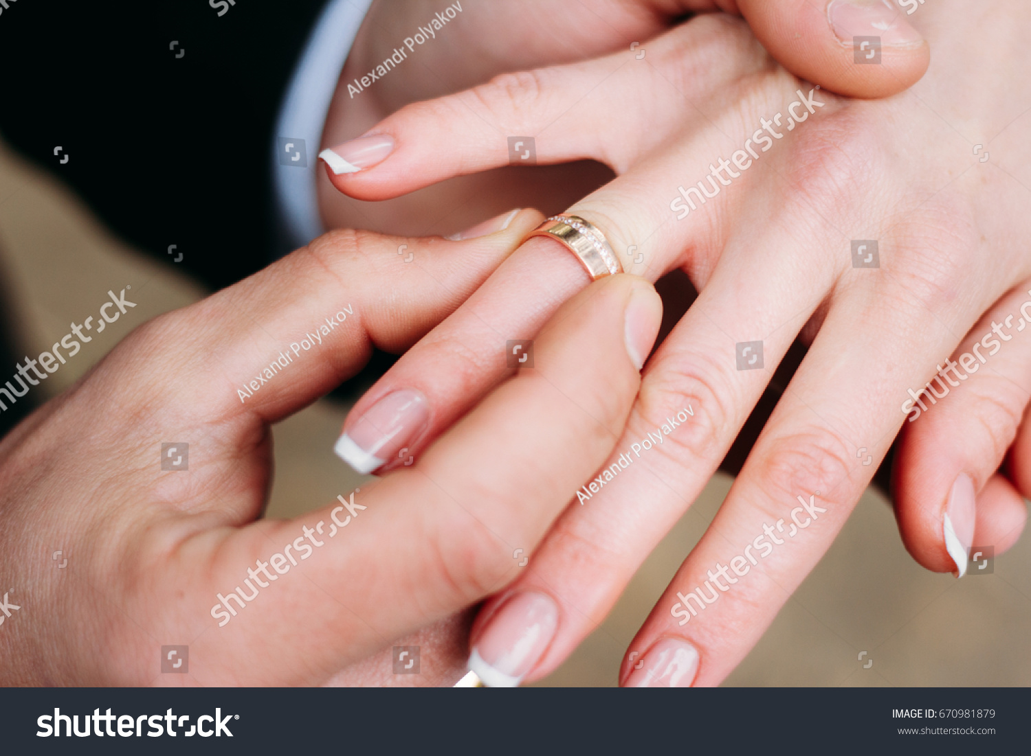 Groom wears a wedding ring on the finger of the bride. Close up ...