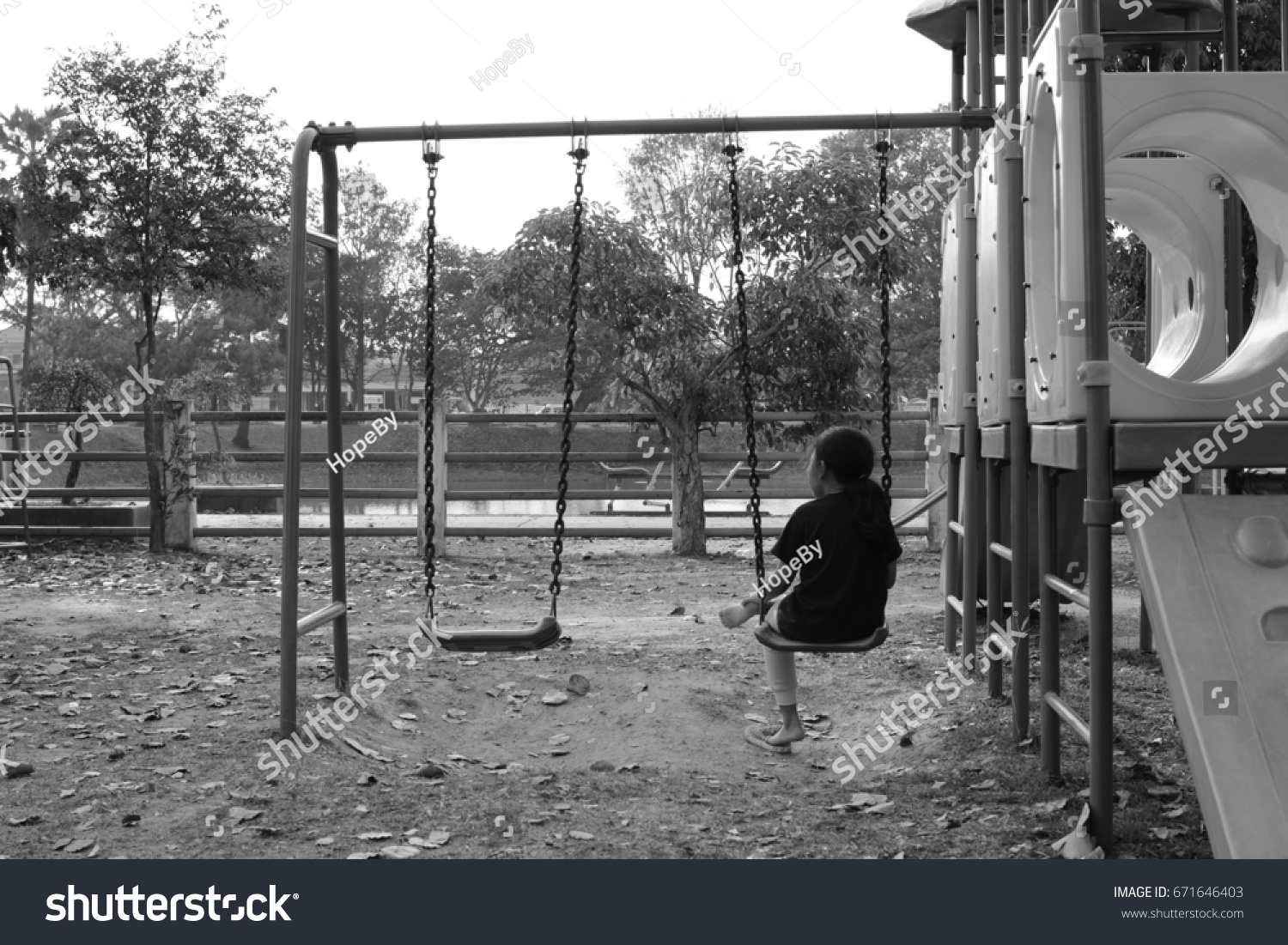 Little asia girl sitting on the swing for wait somebody black and white tone