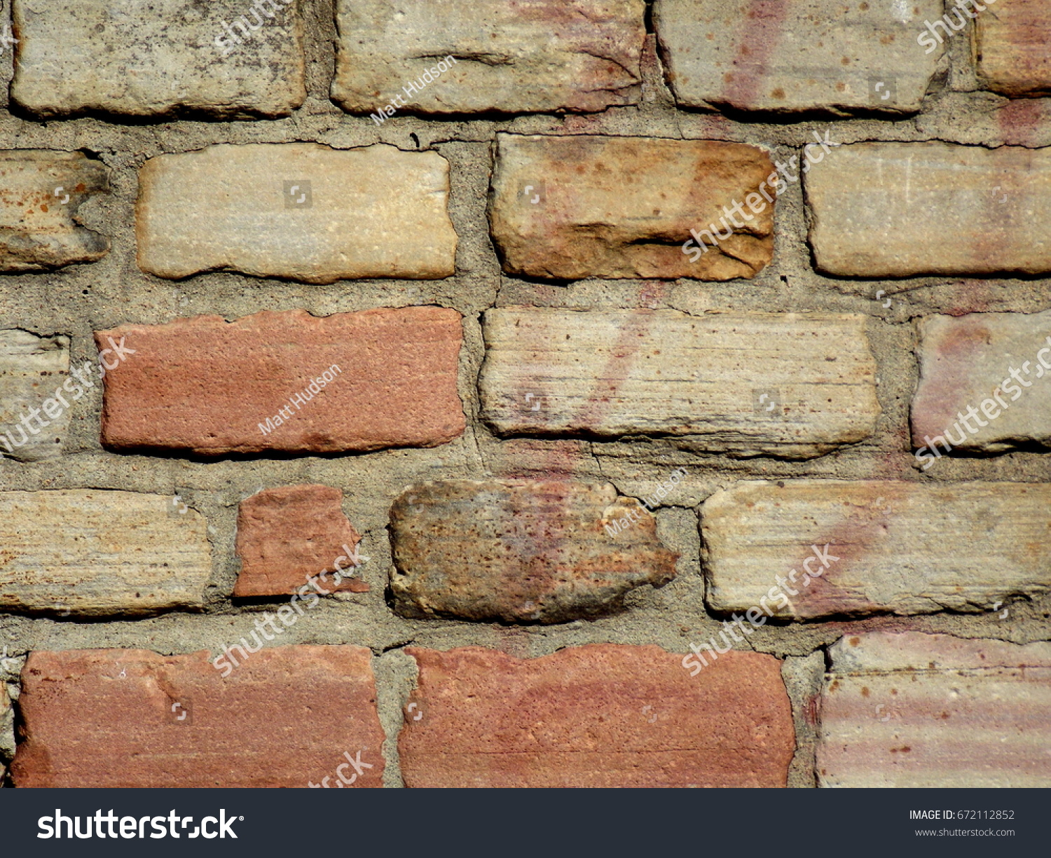 Sandstone block brick wall with fading graffiti background texture