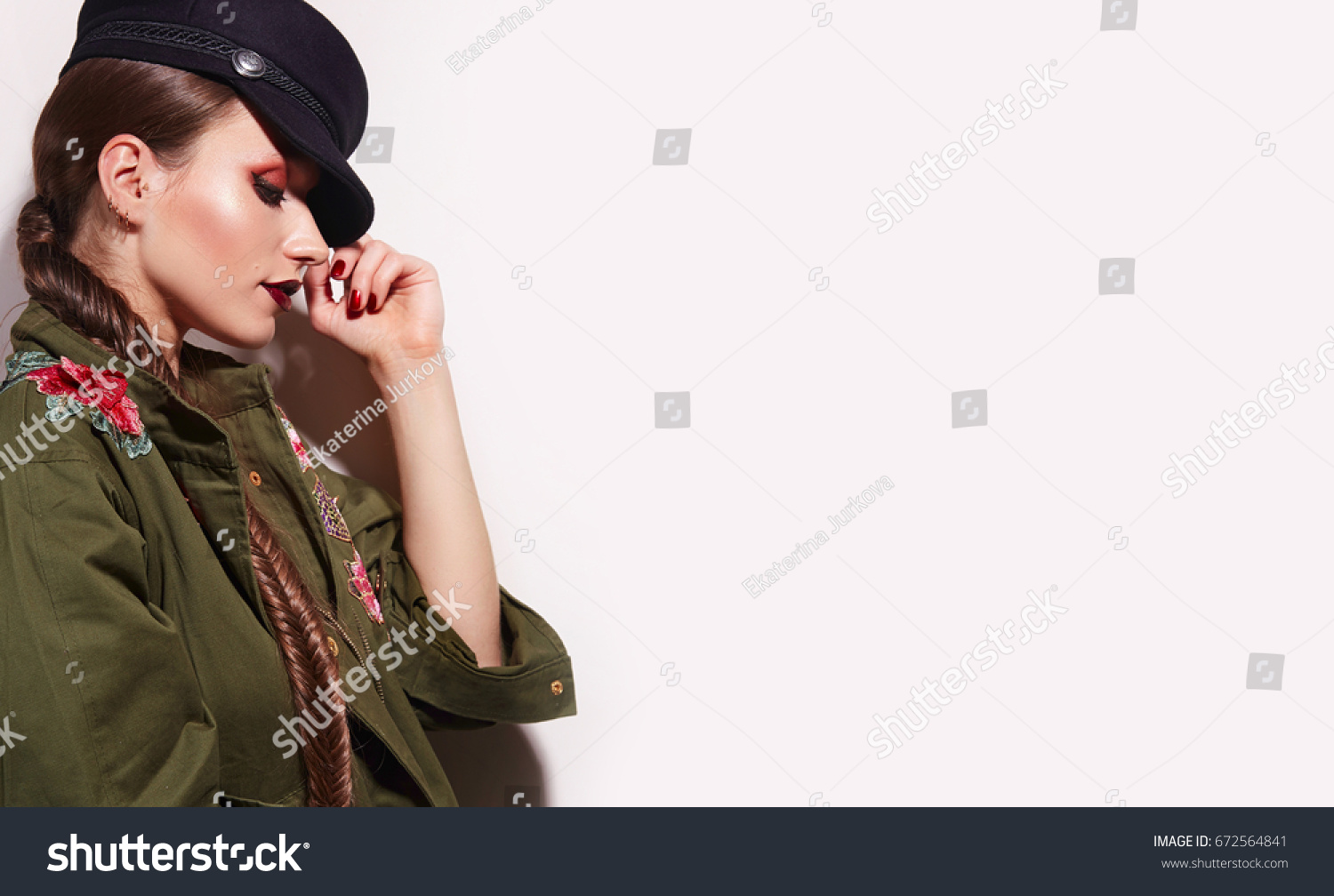 4cfc2e52e5 Beautiful young girl with bright make-up in a green trench coat and a black