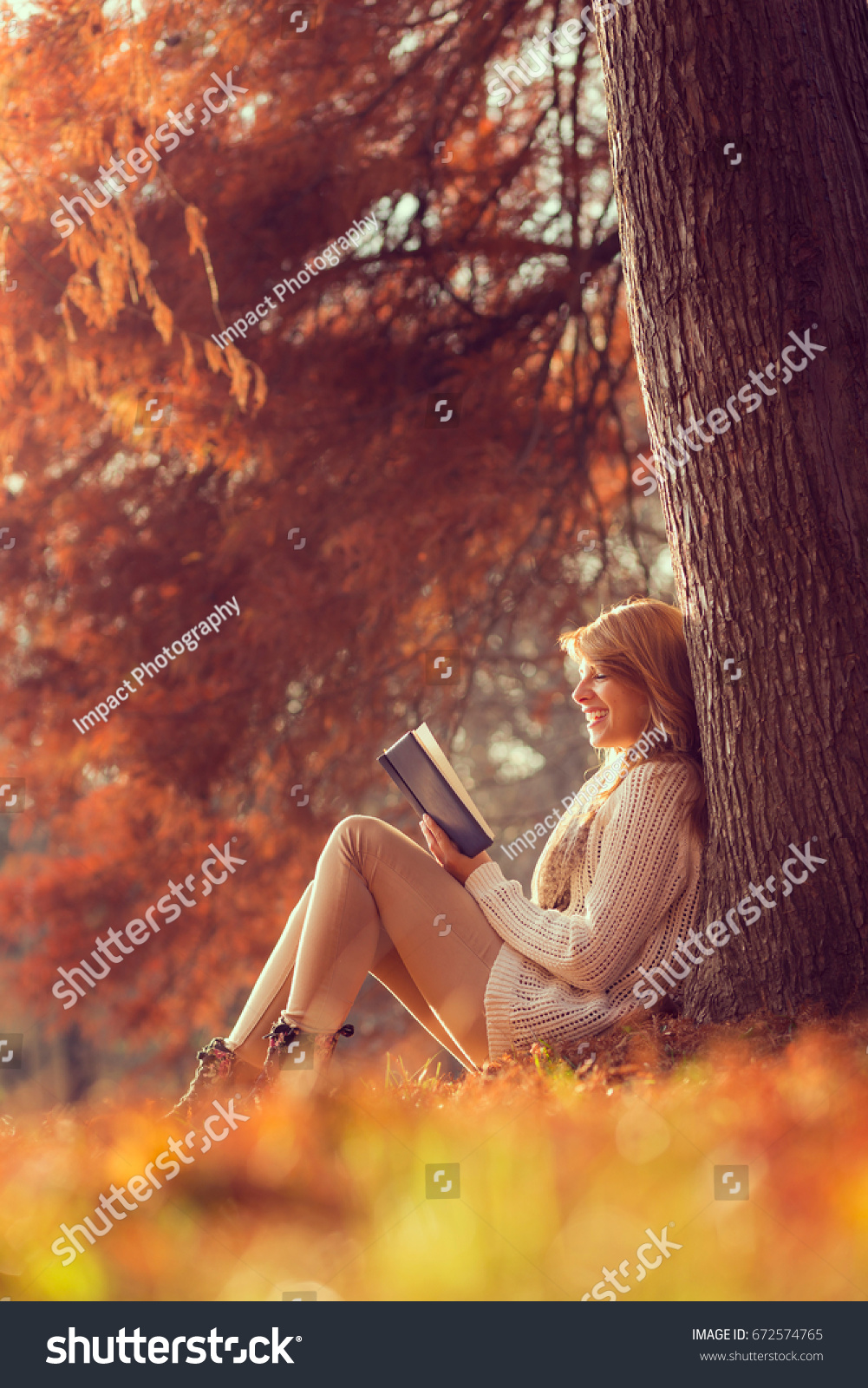 From the book where you might see the beautiful autumn leaves - Beautiful Young Brunette Sitting On A Fallen Autumn Leaves In A Park Reading A Book