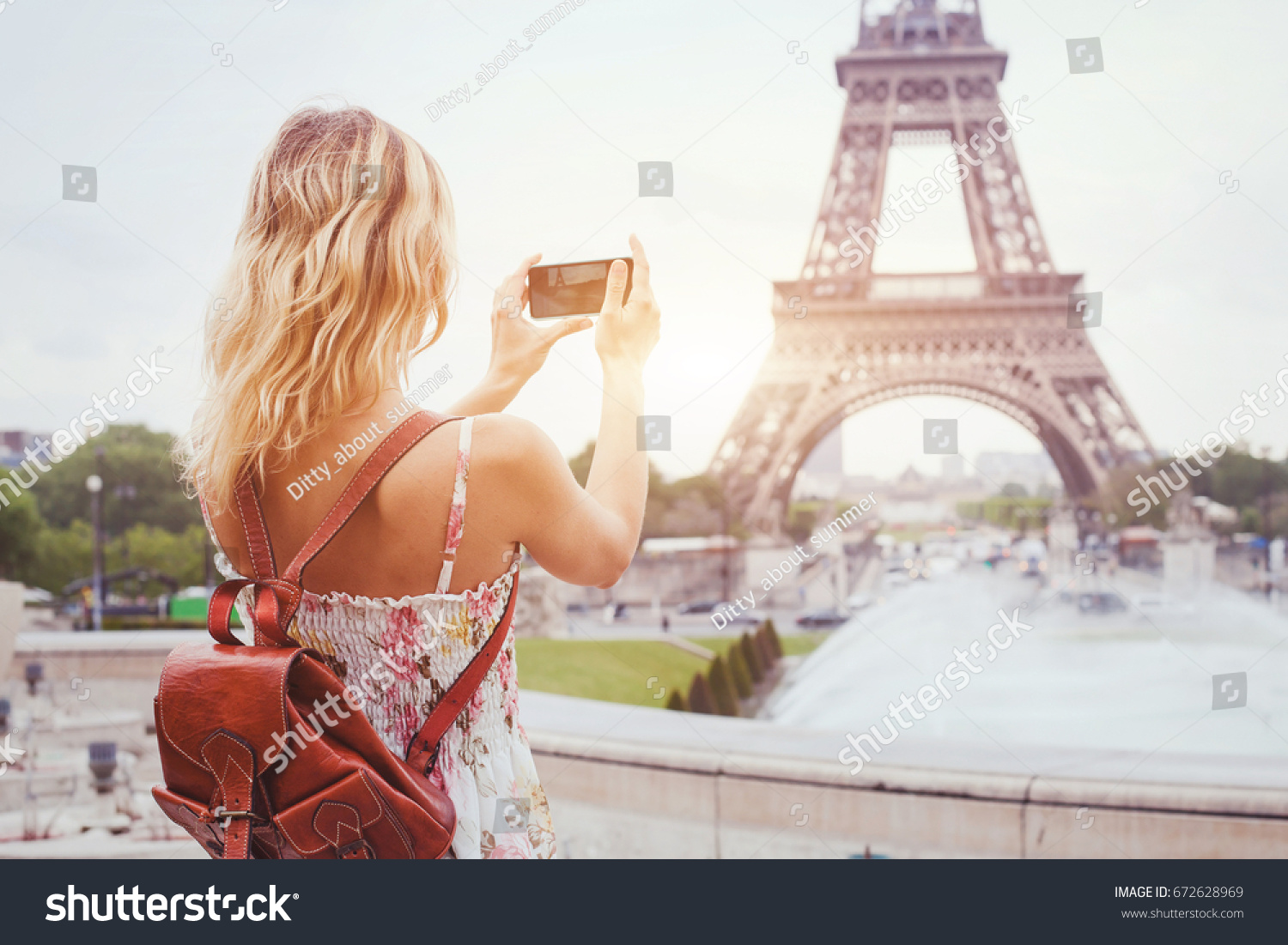 tourist in Paris visiting landmark Eiffel tower, sightseeing in France, woman taking photo on mobile phone #672628969