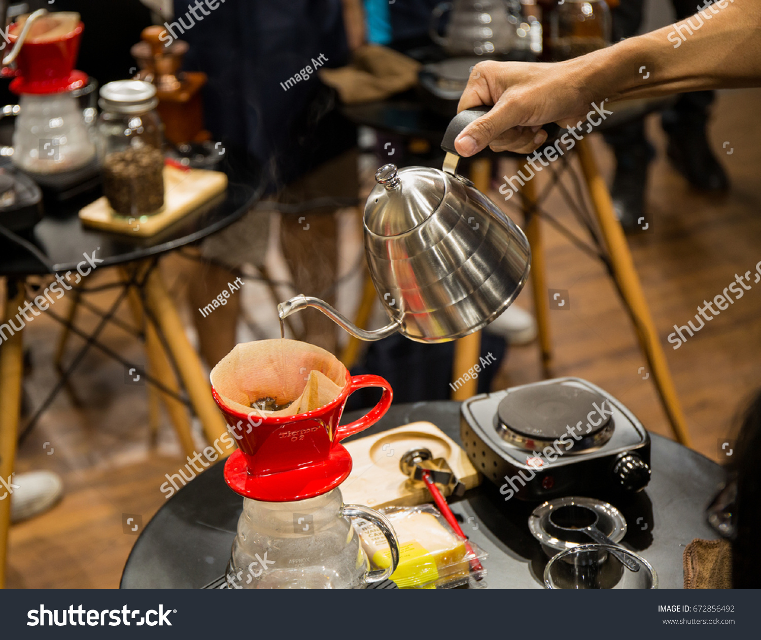 Close up to men and women are pouring hot water from the kettle into the  coffee 53061436e