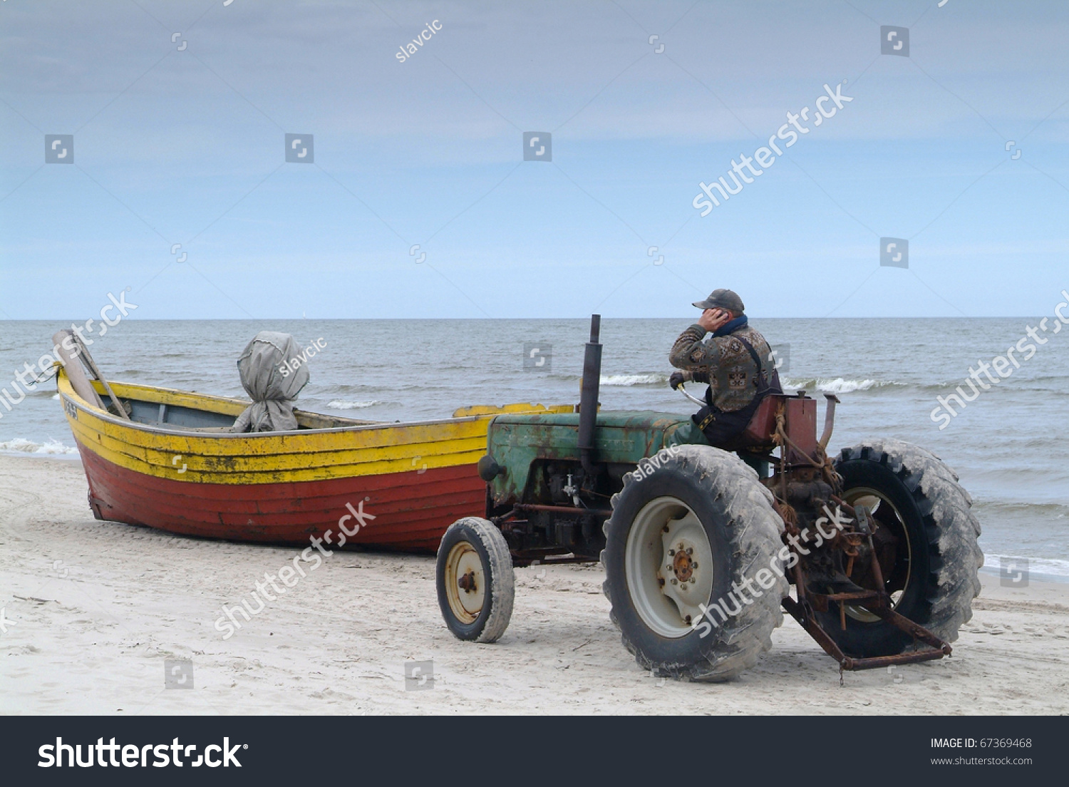 Tractor Pull Boats : Old rusty tractor pulling boat out stock photo
