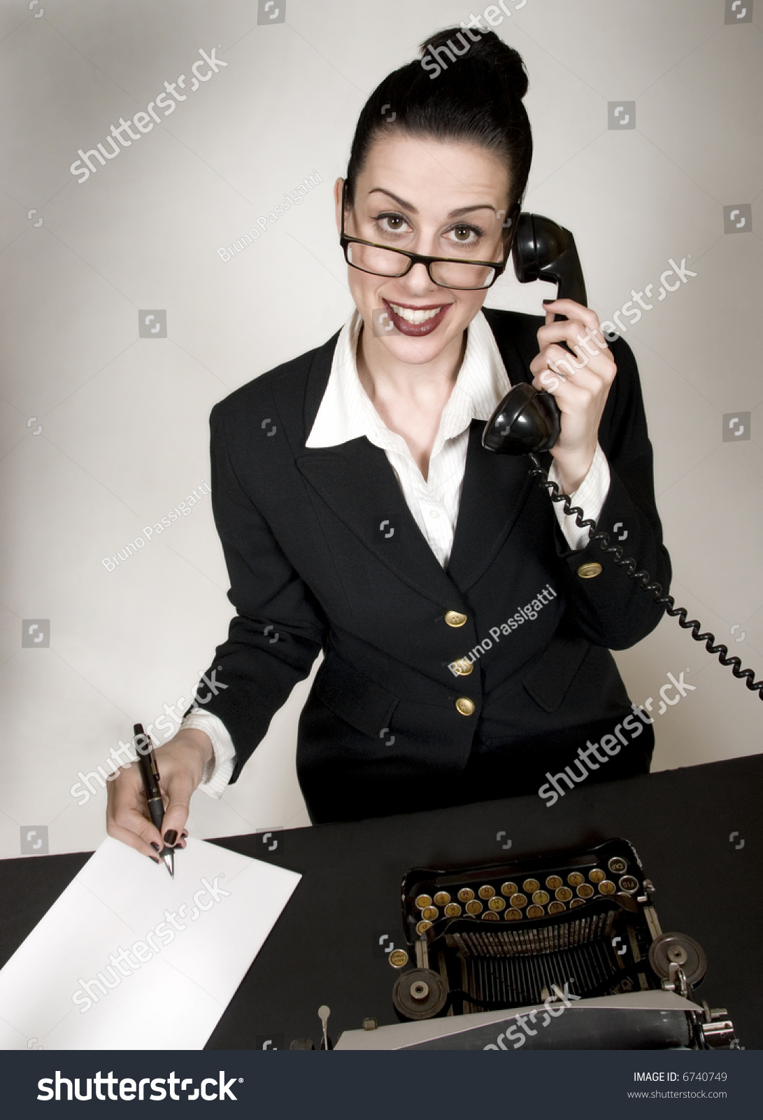 Frustrated office worker on the phone holding stock photo image - Retro Office Worker With Vintage Typewriter And Phone Answering A Call