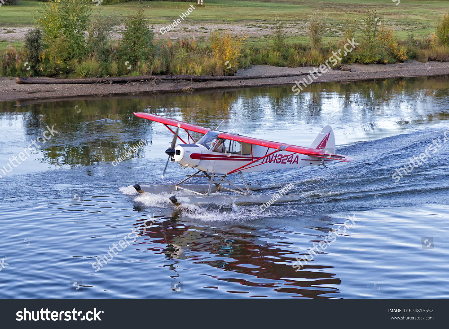 FAIRBANKS, ALASKA, USA - SEPTEMBER 10, 2013: A Piper PA-18-125 lands on the Chena river in Fairbanks, Alaska. Seaplanes are a very popular mode of transportation in the remote Alaskan wilderness.